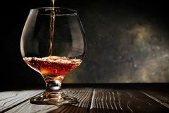 Cognac hälls in i ett exponeringsglas på en gammal mörk träbakgrund Utrymme för fri kopia Selektivt fokusera royaltyfria bilder