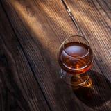 Cognac i exponeringsglas på trät royaltyfri bild