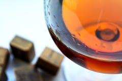 Cognac met donkere chocolade op witte achtergrond stock foto