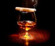 Cognac och cigarr Exponeringsglas av konjak Arkivfoto