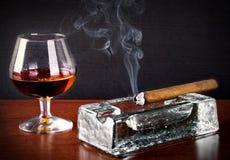 Cognac och cigarr med rök Arkivfoto