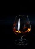 Cognac ou eau-de-vie fine rougeoyant dans un verre ballon Image stock