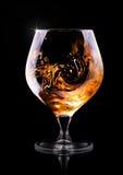 Cognac ou eau-de-vie fine sur un noir Photographie stock libre de droits