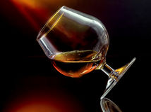 Cognac in overgeheld wijnglas stock foto