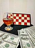 Cognac pengar och schackbräde Royaltyfri Bild
