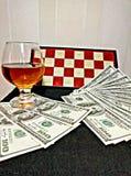 Cognac pengar och schackbräde Fotografering för Bildbyråer