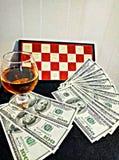 Cognac pengar och schackbräde Arkivbild