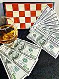 Cognac pengar och schackbräde Arkivbilder