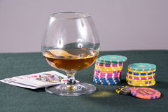Cognac and playing-cards on a table for a poker Stock Photography