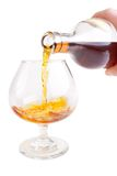 Cognac pour. Into the glass from the bottle, isolated on white background Stock Images