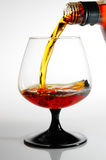 Cognac pour from a bottle in a glass Stock Photos