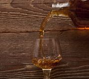 Cognac pour from a bottle in a glass Stock Photo