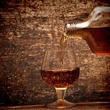Cognac pour from a bottle in a glass Stock Images