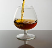 Cognac poured into glass Royalty Free Stock Image