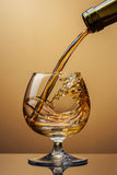 Cognac pouring from bottle into glass with splash on brown Stock Photography