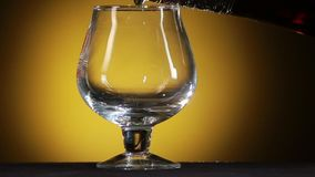 Cognac pouring from bottle into glass with splash stock video