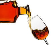 Cognac pouring into the glass. Isolated on white Royalty Free Stock Image