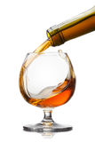 Cognac pouring into glass with splash  on white backgrou Stock Photo