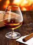 Cognac réchauffant devant l'incendie Image stock