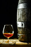 Cognac snifter and an old oak barrel Stock Image