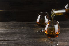 Cognac in two glasses on a dark wooden background Royalty Free Stock Images