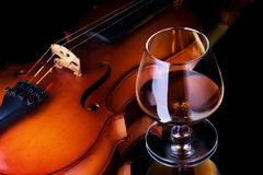 Cognac and violin. Snifter glass of cognac and violin stock photography
