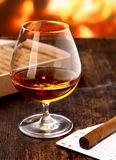 Cognac warming in front of the fire Stock Image