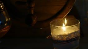 Cognacglas bij het kaarslicht met houten vaten in romantische avond Langzame Motie stock footage
