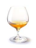 Cognacglas met gouden cognac op een wit stock afbeelding