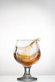 Cognacglas met plons Stock Afbeelding