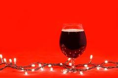 Cognacglasglas donker bier met Kerstmislichten op rode achtergrond stock foto's