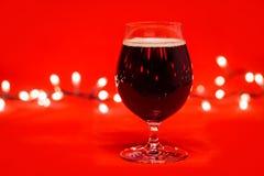 Cognacglasglas donker bier met Kerstmislichten op rode achtergrond royalty-vrije stock fotografie