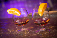Cognak. Two glasses with cognac and orange on a bar Royalty Free Stock Image