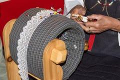 COGNE, ITALIA - 24 DE AGOSTO DE 2016: La mujer en ropa tradicional está haciendo un tombolo típico de la artesanía Foto de archivo