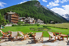 Cogne mountain holiday resort. Aosta Valley, Italy. The holiday resort town of Cogne. Beach chairs on a luxury hotel terrace and garden. Italian Alps, Aosta Royalty Free Stock Photos