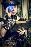 Cognition. Portrait of a beautiful steampunk woman over vintage background royalty free stock images