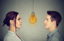 Cognitive skills ability concept, male vs female. Man and woman looking at bright light bulb Stock Image