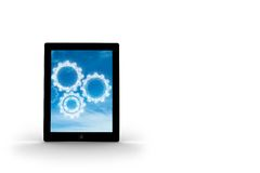 Cogs in clouds on tablet screen Royalty Free Stock Photo
