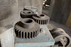 Cogs on dirty machinery in factory. Close up of metal cogs on dirty equipment inside vintage factory Stock Photo