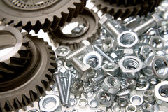 Cogs, nuts & bolts. Steel cogwheels, nuts and bolts Stock Images