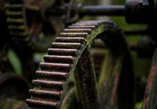 Cogs of a Sawmill. The rusted workings of an old but still operative sawmill are shown in high detail with attractive defocus. Backed by green woodland colours Royalty Free Stock Photo