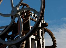 Cogs, wheels and chains. Against a blue sky Royalty Free Stock Photos