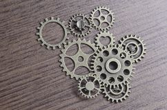 Cogs, Wheels and Gears. It is a still-life photograph of small wheels and gears on a laminated wood table Stock Photos