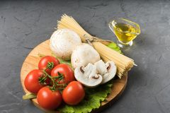 Cogumelos, alface, tomates e espaguetes dos cogumelos na tabela de pedra Fotos de Stock Royalty Free