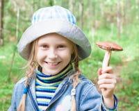 Cogumelos bonitos da colheita da menina na floresta Fotos de Stock Royalty Free