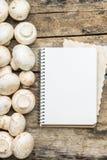 Cogumelos com cozimento do livro ou da folha da receita no fundo de madeira Fotos de Stock Royalty Free
