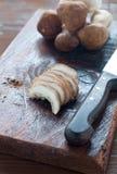 Cogumelos crus em uma placa de corte de madeira pronta para ser cortado Fotografia de Stock