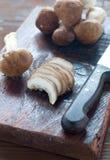 Cogumelos crus em uma placa de corte de madeira pronta para ser cortado Imagem de Stock