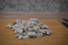 Cogumelos descascados e cortados, preparados para uma refeição do peito de frango frito com cogumelos e salada imagem de stock royalty free