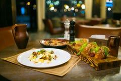 Cogumelos do crepe e aperitivos da carne na placa de corte de madeira foto de stock